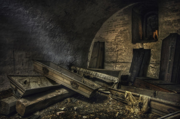 The-black-figure-in-an-old-abandoned-crypt-full-of-mostly-empty-coffins.jpg