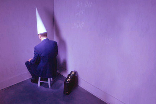 businessman-sitting-in-corner-with-dunce-hat.jpg